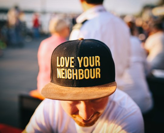 Guy wearing hat that says love your neighbor