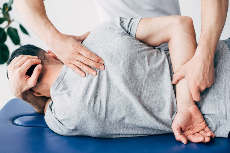 back-view-of-chiropractor-massaging-back-of-man-ly-69N6EHY.jpg